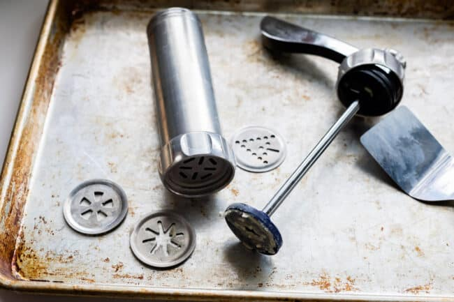 metal cookie press on a baking sheet