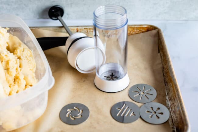 oxo cookie press on a baking sheet with cookie dough on the side.