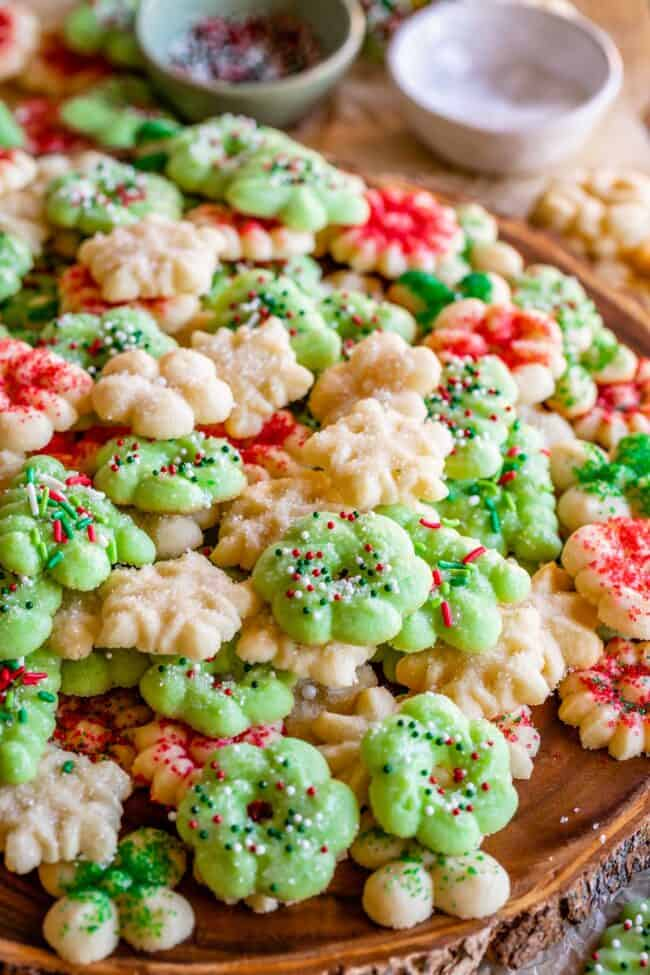 Christmas spritz cookies laid out on a wooden board with sprinkles