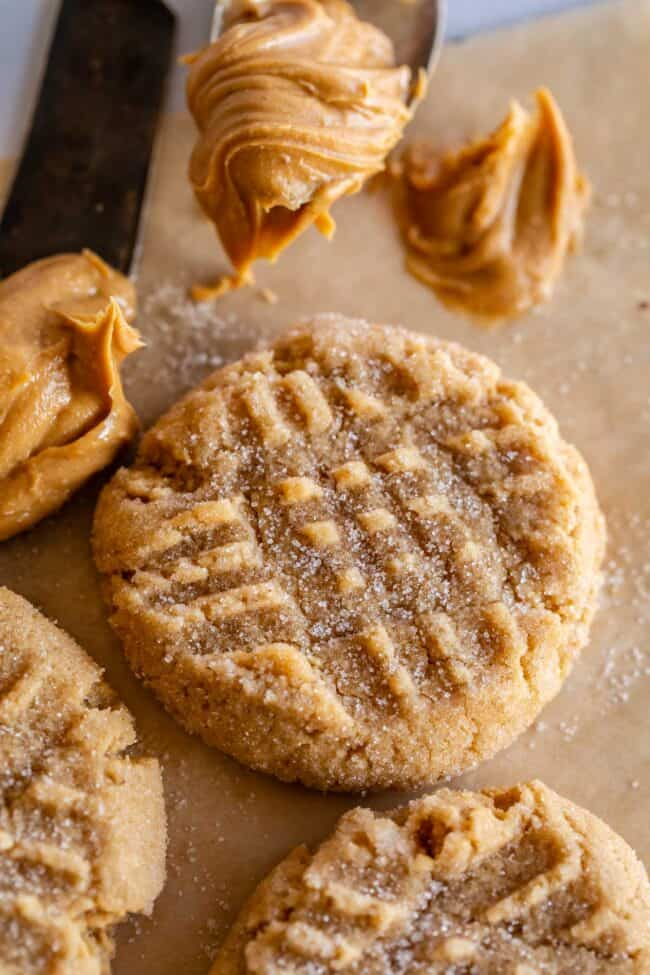 best peanut butter cookies on a tray, with a scoop of peanut butter on the side