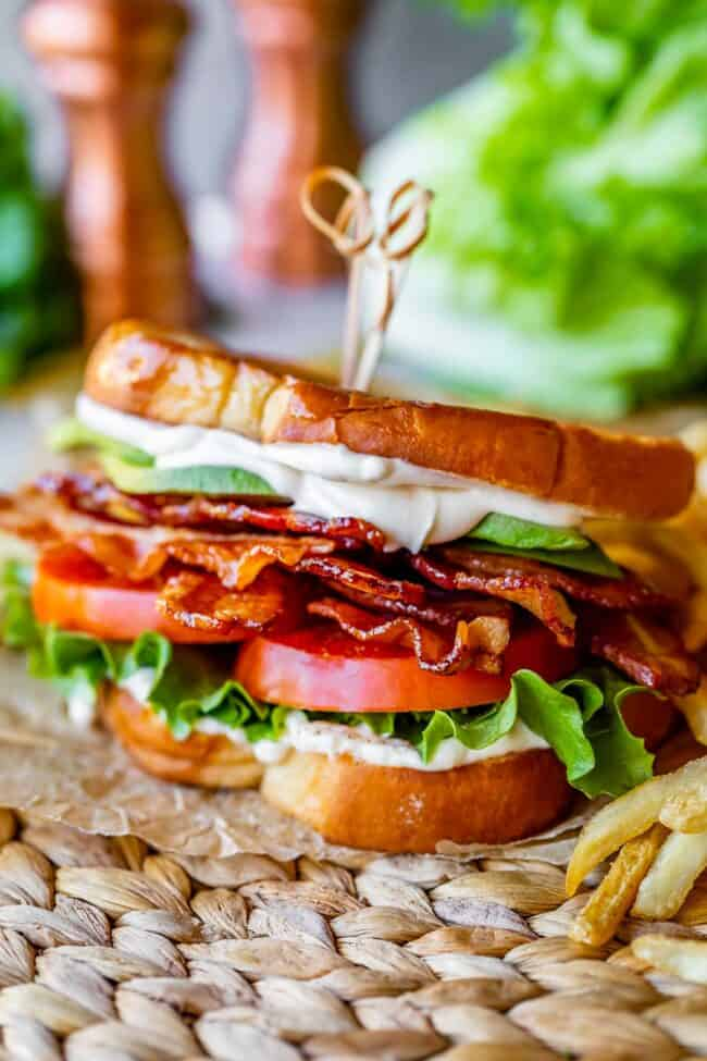 blt sandwich with french fries, on parchment paper with lettuce and salt and pepper shakers in the background