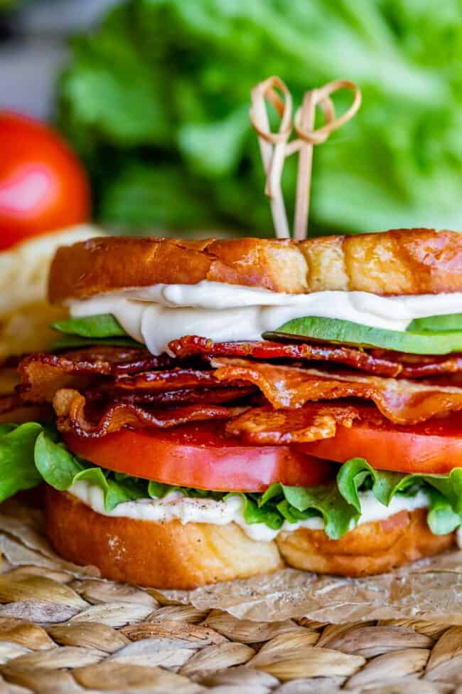 avocado BLT with toothpicks on top, on parchment paper with lettuce in the background