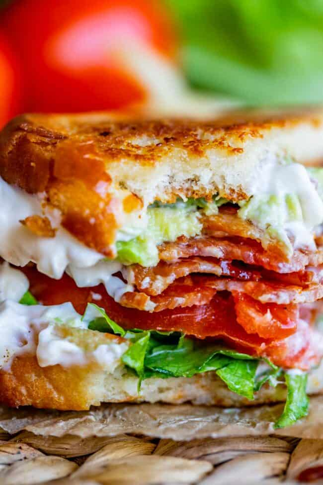 BLT sandwich with toasted bread and mayo, with a bite taken out