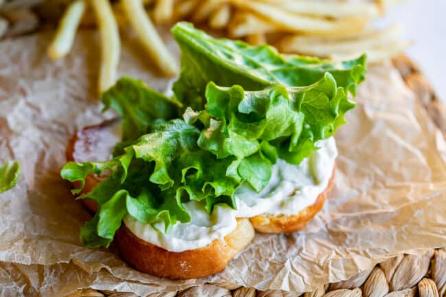 green leaf lettuce on bread with mayonnaise on paper with fries