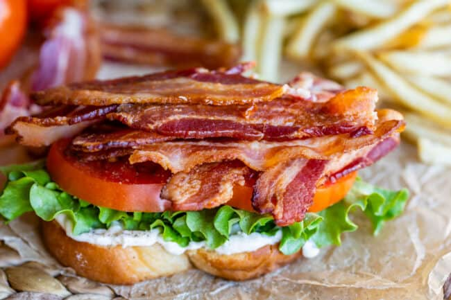 bacon, tomato, lettuce, mayo, white bread, with fries in the background