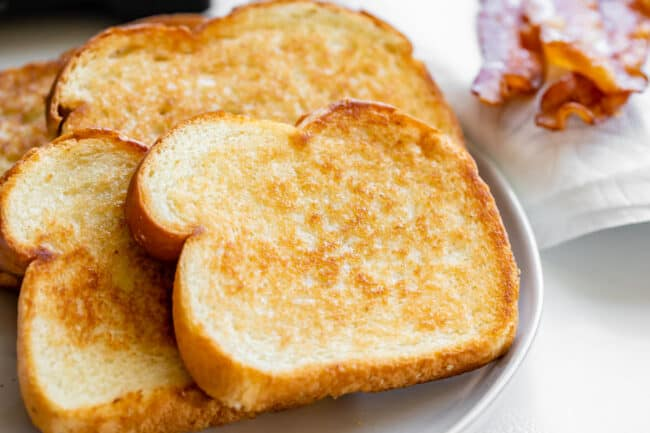 toasted white bread with butter on a white plate