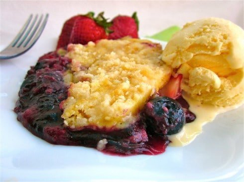 Easy Berry Cobbler on a plate with ice cream and strawberries