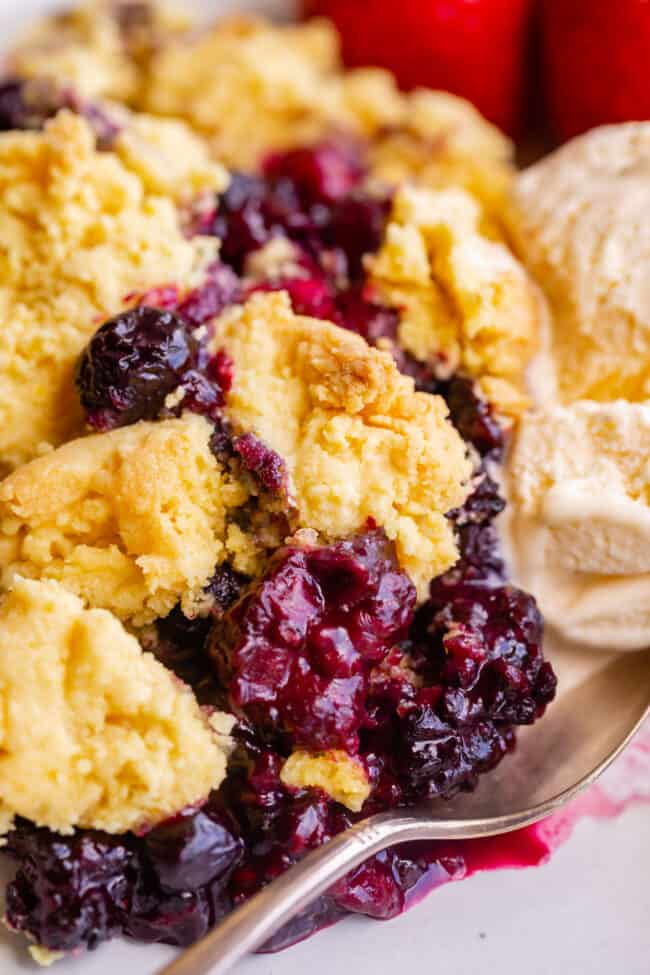mixed berry cobbler on a plate with ice cream