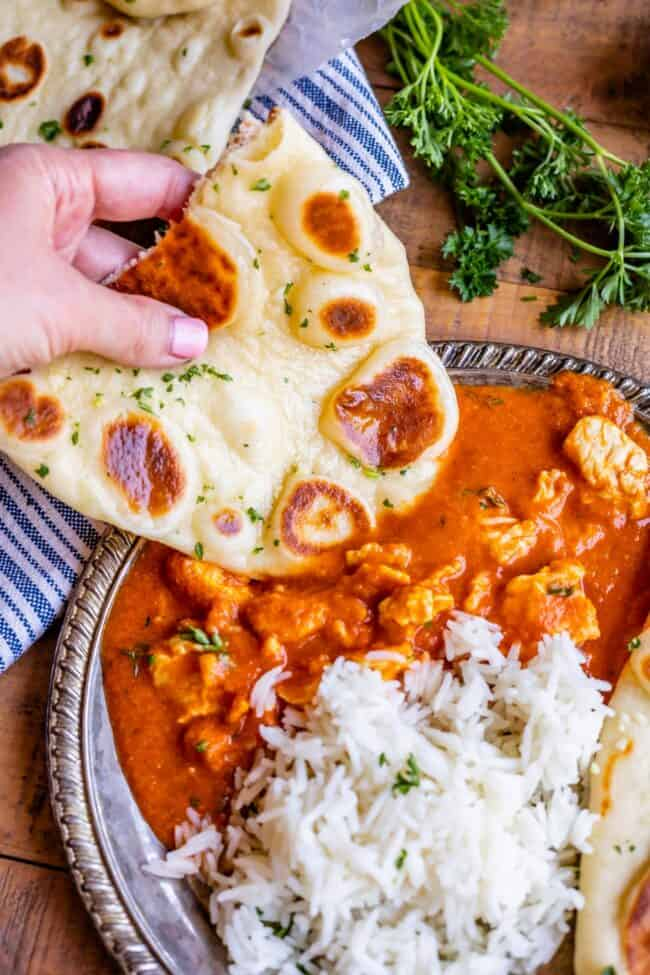 homemade naan dipped in curry on a plate