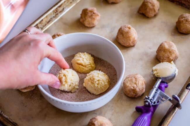 rolling cookie dough in cinnamon sugar and placing on a pan