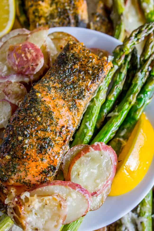 Overhead shot of pink salmon with lemon, asparagus, and creamy potatoes.