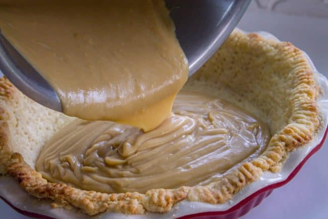 filling a blind baked pie crust with cream filling