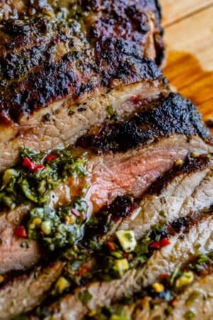 close up of tender flank steak broiled on top with herbs