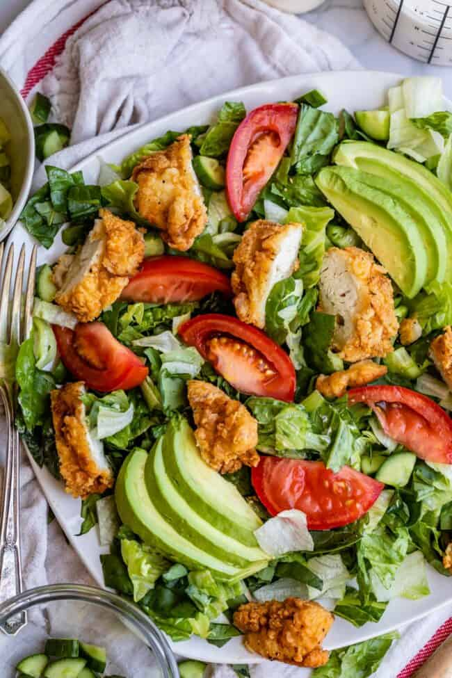 fried chicken salad recipe on a plate with avocados and tomatoes