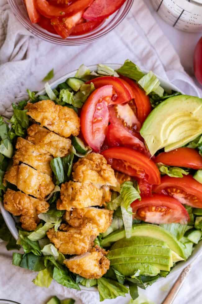 Crispy chicken salad in a bowl with tomato and avocado