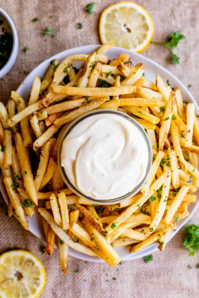 garlic aioli sauce in a jar with a plate of fries