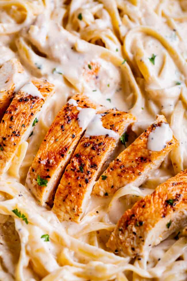 close up picture of sliced chicken in creamy alfredo sauce