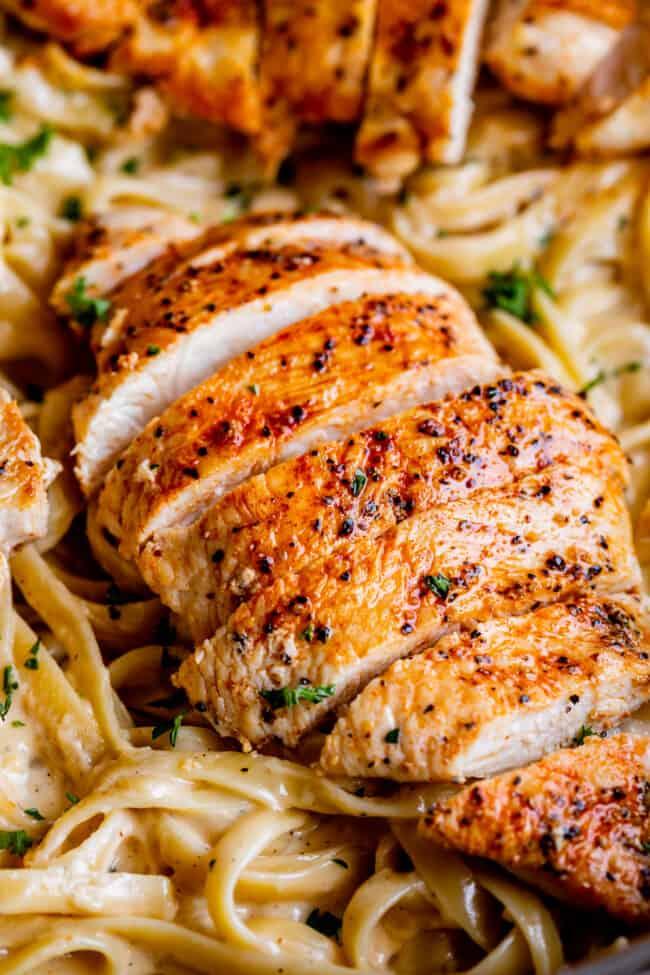 close up of sliced chicken on fettuccine alfredo