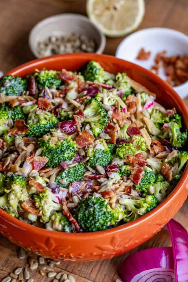 Broccoli salad in an orange bowl with red onion and a lemon