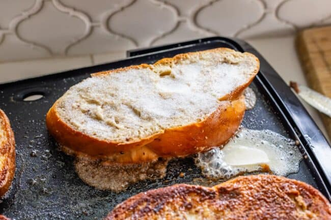 brioche french toast frying on an electric griddle, with sugar on top to caramelize