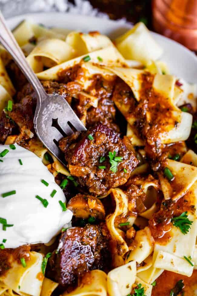 a fork lifting up traditional beef stroganoff from a plate