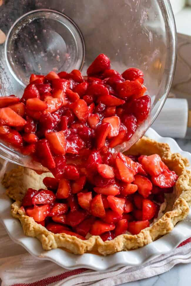 pouring strawberries into a pre baked pie shell