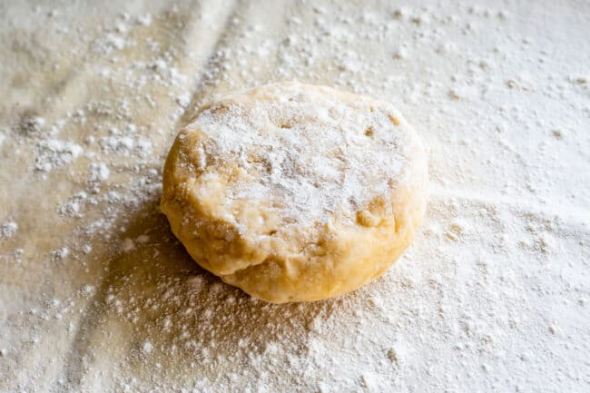 disc of chilled pie dough sprinkled with flour ready to be rolled out