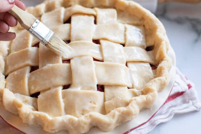 brushing milk and egg on top of lattice pie crust