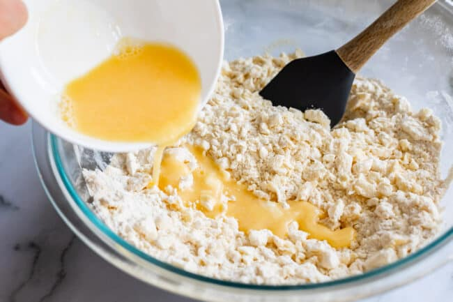 pouring egg and ice water into pie crust dough