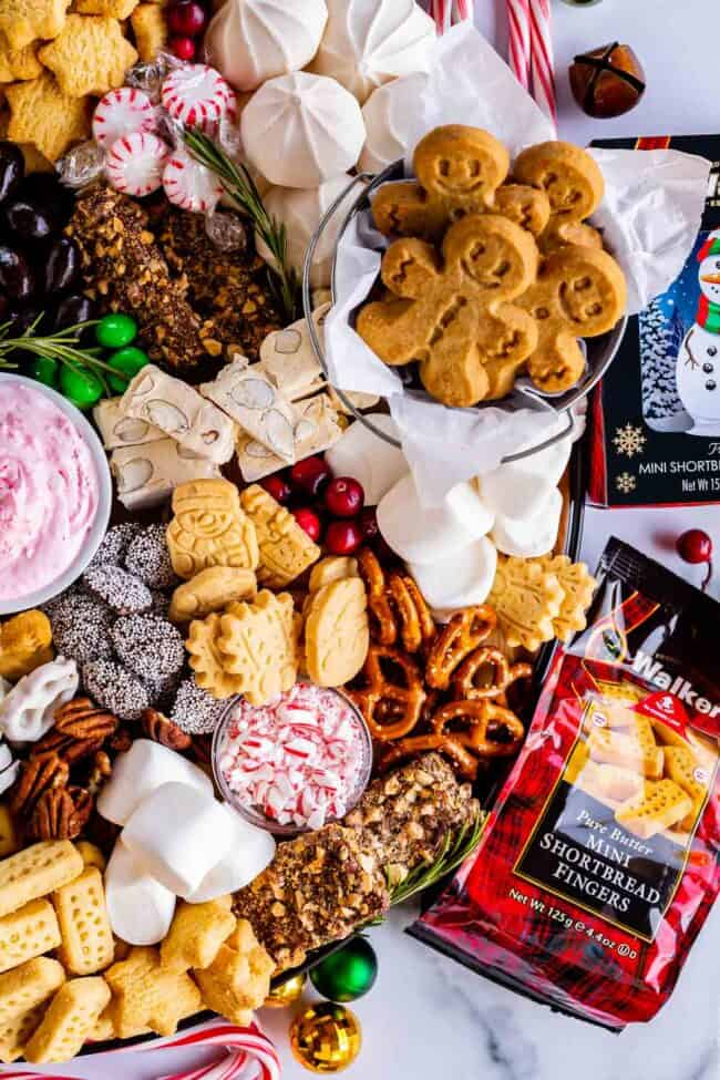 how to make a dessert charcuterie board with shortbread, cranberries, gingerbread, pretzels, candy canes, pecans, meringues