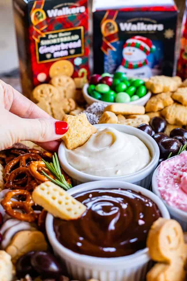 dipping shortbread into a marshmallow creme dip on a dessert charcuterie board
