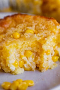 creamed corn casserole on a plate with a bite taken out