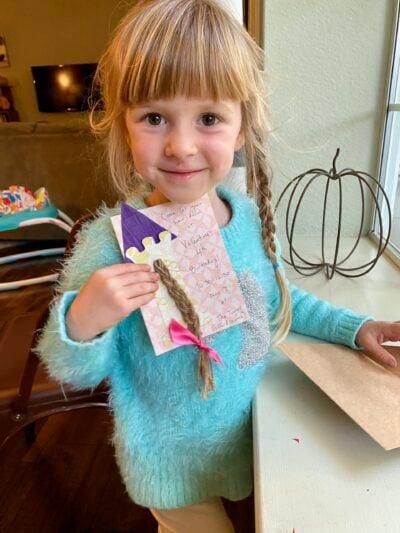 Daughter holding homemade rapunzel birthday card