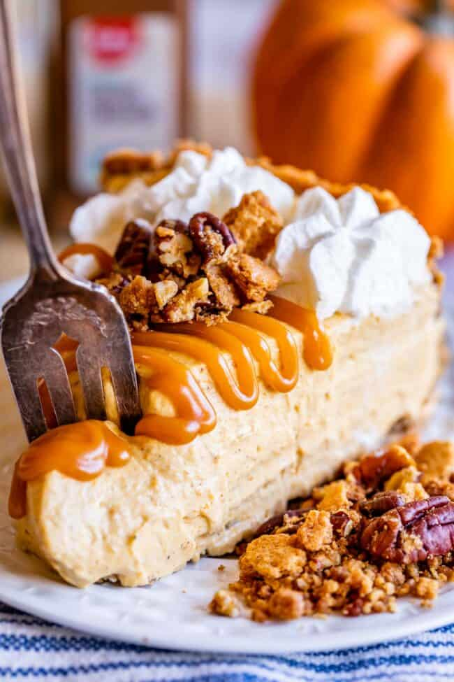 slice of easy no bake pumpkin cheesecake with caramel drizzle, pecans, and whipped cream
