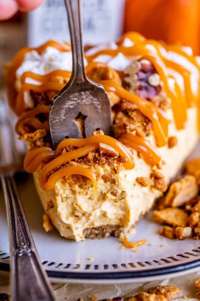 slice of easy no bake cheesecake drizzled with caramel, with a fork taking a piece