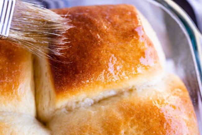 brushing butter on a golden dinner roll