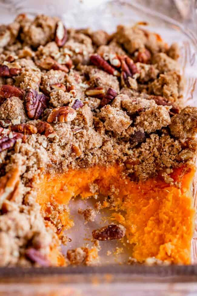 sweet potato casserole with pecans in a glass pan with sweet potatoes exposed