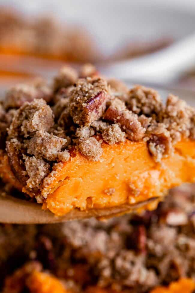 sweet potato casserole with pecans being lifted from the pan on a spoon