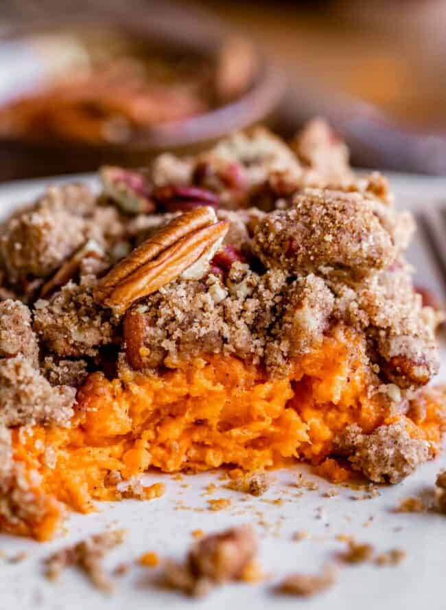 sweet potato casserole with pecan topping on a plate with bites taken out
