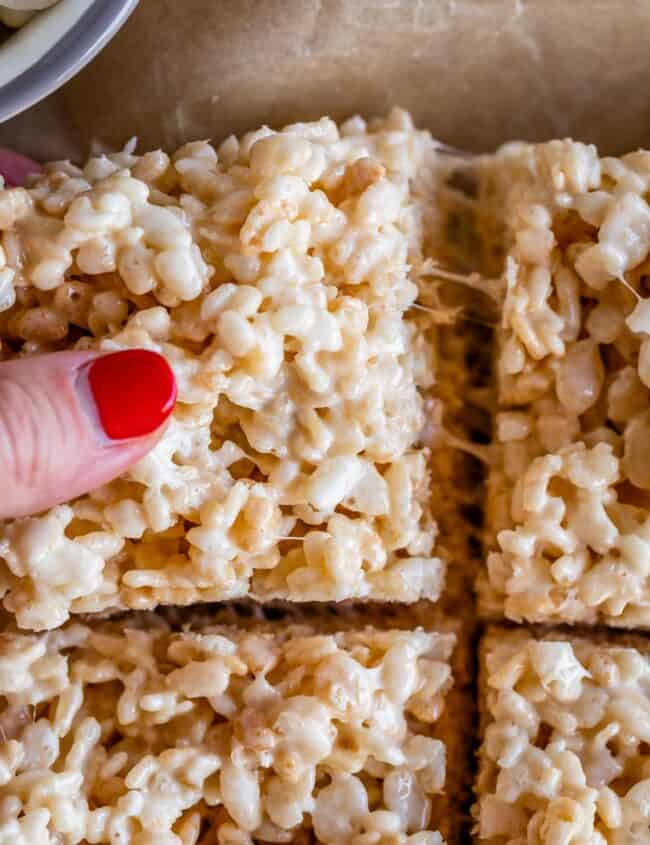 pulling a rice crispy treat away with fingers