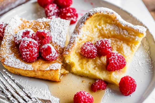 two pieces of German pancakes on a plate with raspberries