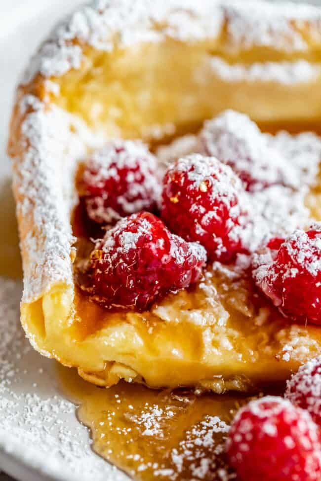 dutch baby with raspberries, syrup, and powdered sugar
