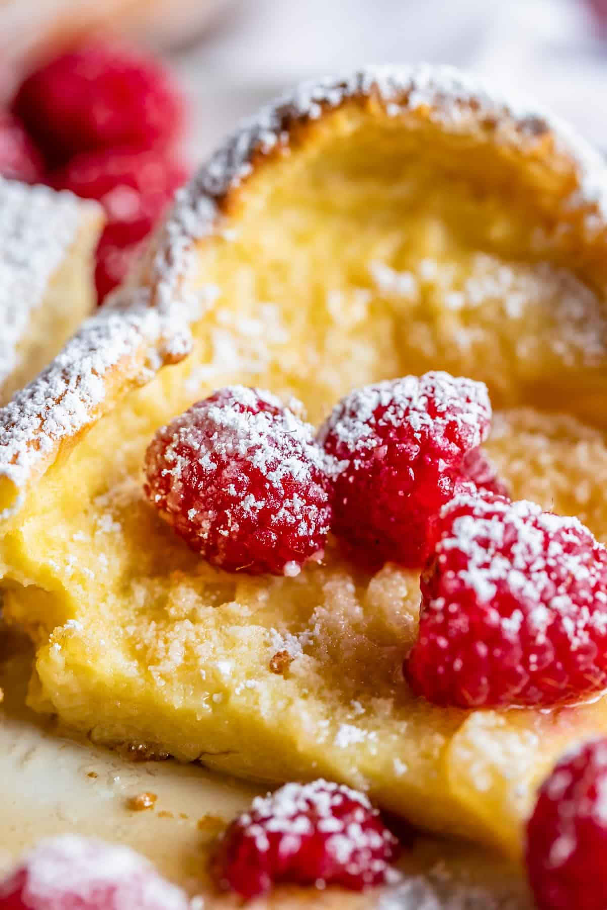 puffy pancakes on a plate with raspberries
