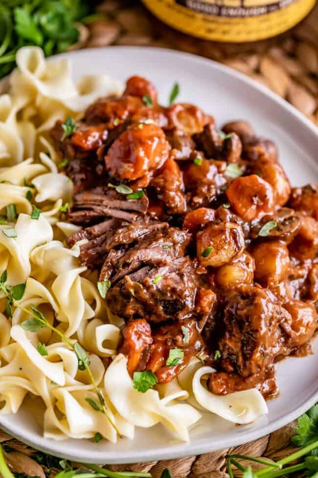 what to serve with beef bourguignon: egg noodles on a plate with the stew
