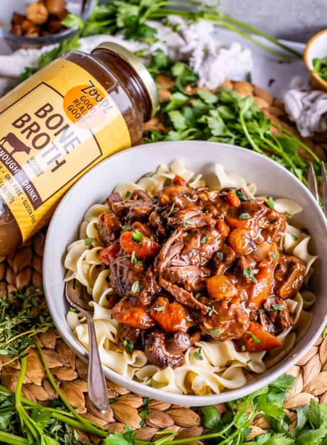 a bowl of egg noodles topped with Julia Child's beef bourguignon, next to a jar of Zoup! Broth
