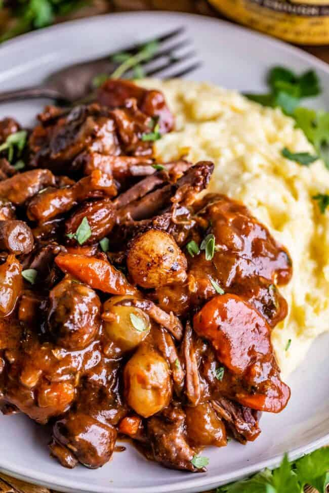 beef bourguignon stew on a plate next to mashed potatoes, with a fork in the background