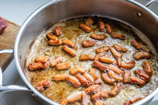 salt pork being fried in a pan