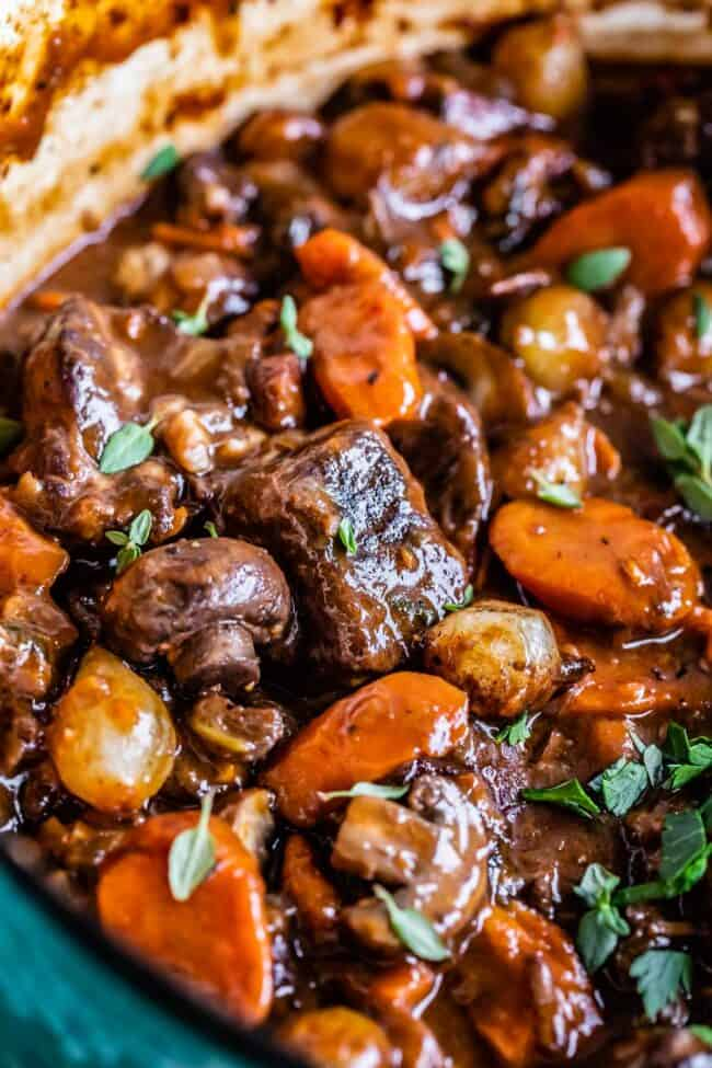 beef bourguignon recipe with beef, mushrooms, carrots, pearl onions, in a teal pot