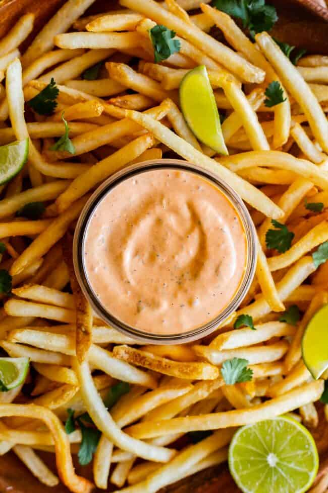 chipotle mayo recipe in a jar surrounded by fries and lime slices