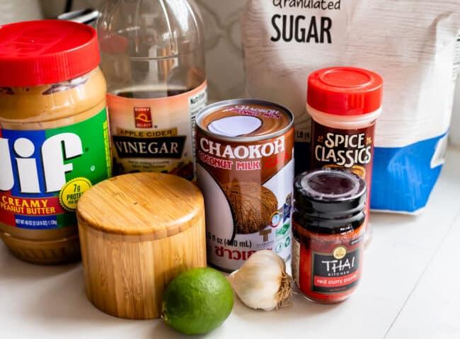 peanut butter, vinegar, salt, coconut milk, lime, garlic, red curry paste, sugar, on a white counter